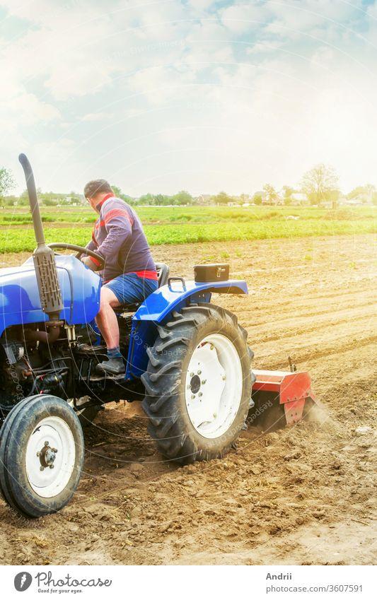 Ein Landwirt auf einem Traktor bearbeitet ein Feld. Der Boden wird gemahlen, zerkrümelt und gemischt. Landwirtschaft, Anbau von Bio-Gemüse. Lockern der Oberfläche, Kultivieren des Bodens für weitere Anpflanzungen.