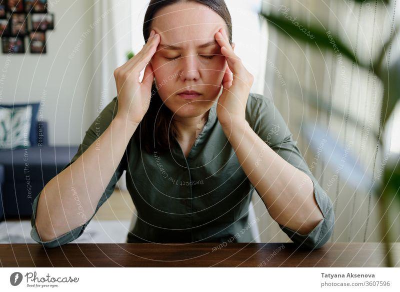 Frau denkt. Hände auf dem Kopf halten. Müde, Stress Denken heimwärts müde betend traurig Problemlösung arbeiten Person im Innenbereich Menschen Kaukasier