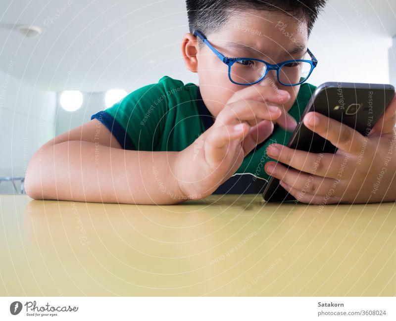 Ernsthafter Junge spielt auf Smartphone Kinder ernst Telefon spielen Spiel Schweiß asiatisch Hand Technik & Technologie klug jung aufrichtig Internet Mobile