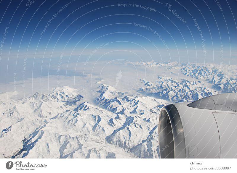 Über den Bergen ... fliegen Flugzeug Berge u. Gebirge Schnee Himmel Wolken Alpen Düsenflugzeug Triebwerke Ferne reisen Horizont Luftverkehr blau