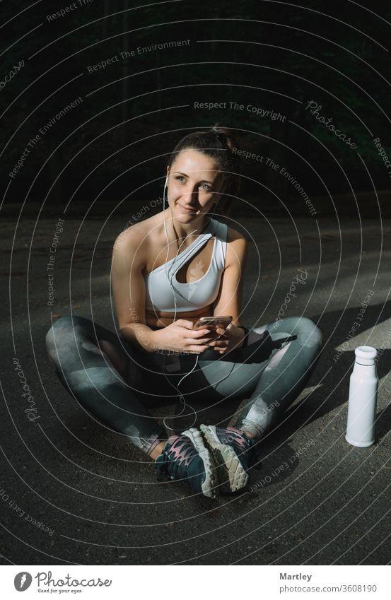 Porträt eines jungen, fitten, hübschen Mädchens, das auf der Straße sitzt und Textnachrichten auf dem Smartphone tippt. Frau, die ihr Telefon nachmittags auf der Straße benutzt.