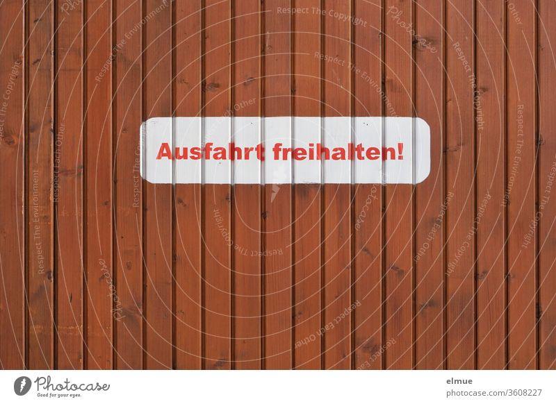 """weißer Aufkleber mit roter Druckschrift """"Ausfahrt freihalten!"""" an einer braunen Holzwand Parkverbot Schrift Buchstabe privat Einfahrt Tor Aufforderung"""