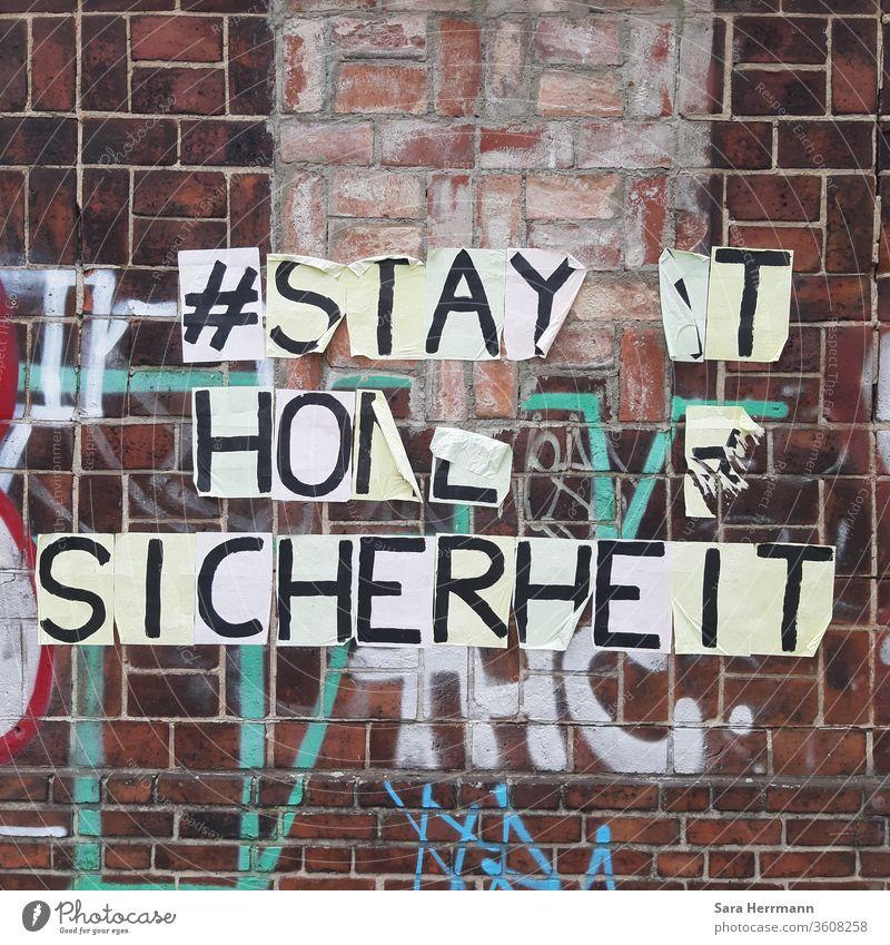 Ein sich ablösender Schriftzug an einer Backsteinmauer Sicherheit stay at home Berlin Corona-Virus Schutz streetart Hashtag