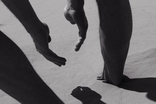 Ein Hauch von Sommer. Mann am Strand in Nahaufnahme, Detail des Körpers, Geste der Hände und Beine, tiefer Schatten. Sommerliche Stimmung, Mann spielt mit dem Sand. Heißes Wetter.