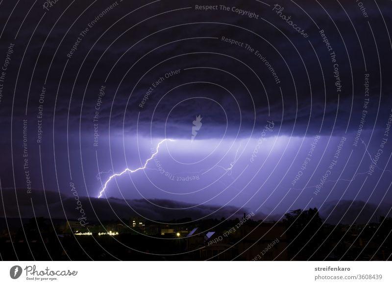 Die mächtigen Wolken über der Stadt rissen auf, so dass das helle Licht der Blitze sichtbar werden konnte Gewitter Nacht Donner Unwetter Außenaufnahme Farbfoto