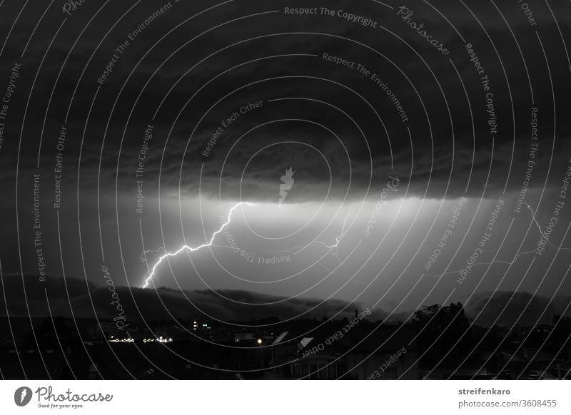 Gewaltige Blitze werden am schwarz-weißen Himmel zwischen den mächtigen Wolkenschichten sichtbar Nacht Gewitter Unwetter Außenaufnahme Donnern Gewitterwolken