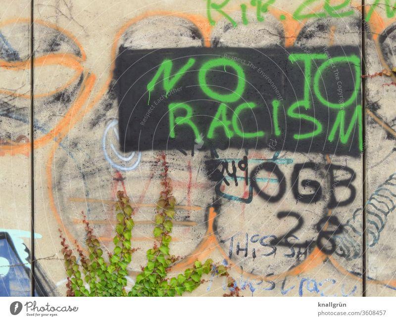 """Grünes Graffiti """"NO TO RACISM"""" auf schwarzem Rechteck auf einer bunten Wand Rassismus Politik & Staat Gesellschaft (Soziologie) protestieren Protest"""