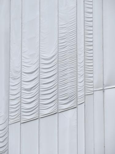 Weiße, zum Teil geraffte lange Stoffbahnen verhüllen ein Bauwerk, das restauriert wird. Verhüllung Schutz Strukturen & Formen Muster Gerafft Faltenwurf