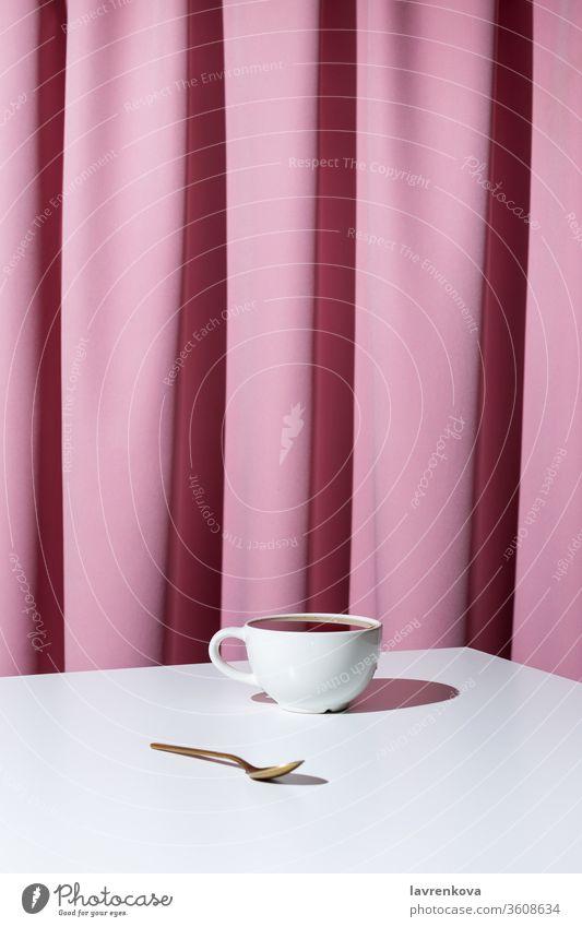 Tasse Tee oder Kaffee auf weißem Tisch vor rosa Draperie, selektiver Fokus Aroma Getränk schwarz Koffein Gardine Vorhang trinken Espresso heiß im Innenbereich