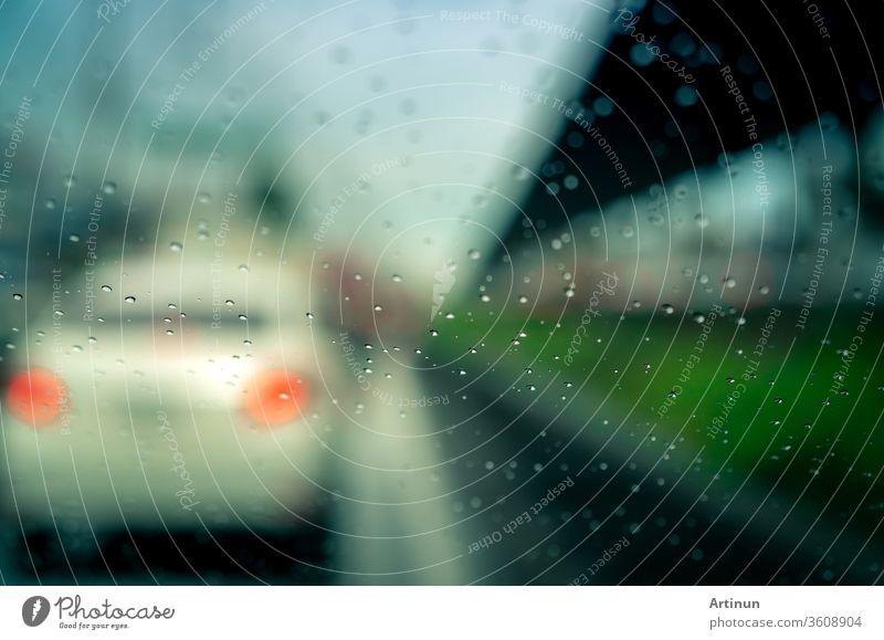 Regentropfen auf der Windschutzscheibe. Auto fährt an einem regnerischen Tag auf Asphaltstrasse. Windschutzscheibe eines Autos mit Regentropfen auf Glaswindschutzscheibe. Verkehrsstau an einem Regentag. Schlechtes Wetter an einem stürmischen Tag. Reisen mit dem Auto.
