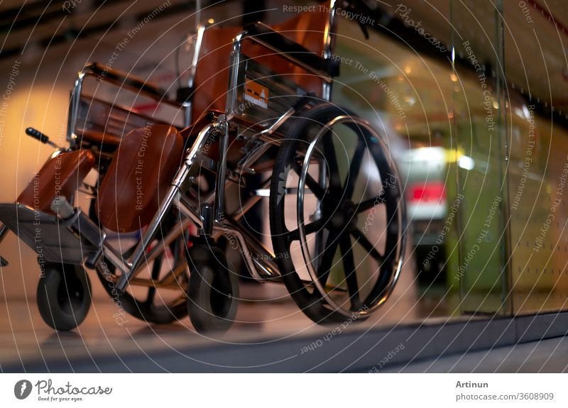 Verschwommener leerer Rollstuhl in der Nähe des Aufzugs in einem Privatkrankenhaus für Dienstpatienten und Behinderte. Medizinische Ausrüstung im Krankenhaus zur Unterstützung von behinderten Menschen. Rollstuhl mit Rädern für die Patientenversorgung.