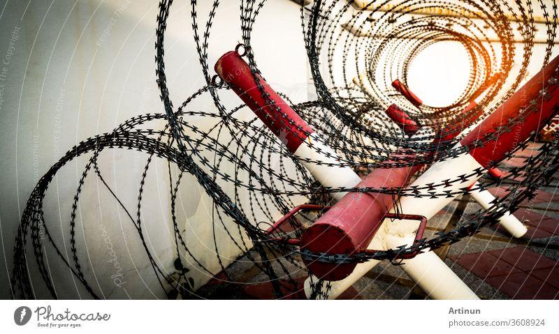 Stacheldrahtzaun. Gefängnis oder Gefängnismauer. Sicherheitssystem. Private Zone oder militärische Gefahrenzone. Verbotenes Tor oder Eingang. Verbotener Bereich. Rot-weiße Farbe auf Stange mit gerolltem Stacheldrahtzaun.