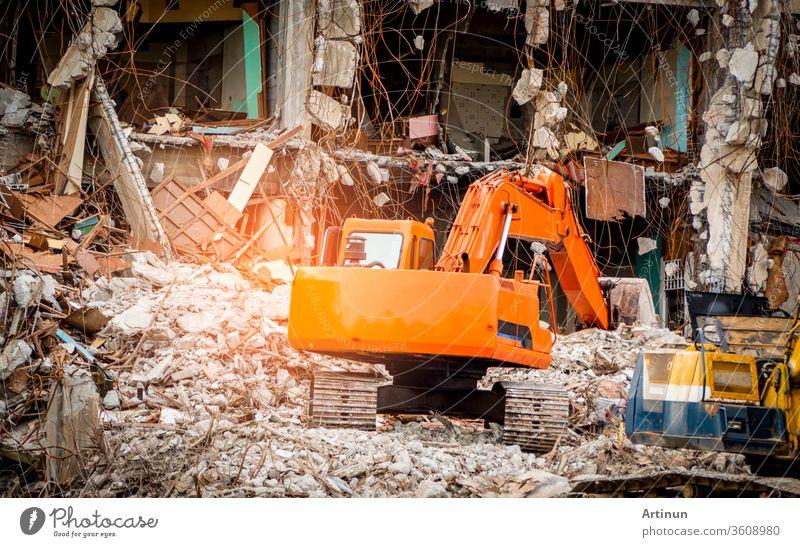 Zerstörte Bauindustrie. Gebäudeabriss durch Explosion. Verlassenes Betongebäude mit Schutt und Schrott. Ruine durch Erdbeben. Beschädigtes oder eingestürztes Gebäude durch Hurrikan-Katastrophe. Tieflöffelbagger.