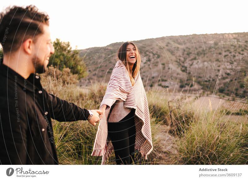 Begeistertes multiethnisches Paar auf dem Hügel Lachen Witz Zusammensein Spaß haben Berge u. Gebirge Händchenhalten heiter Partnerschaft rassenübergreifend