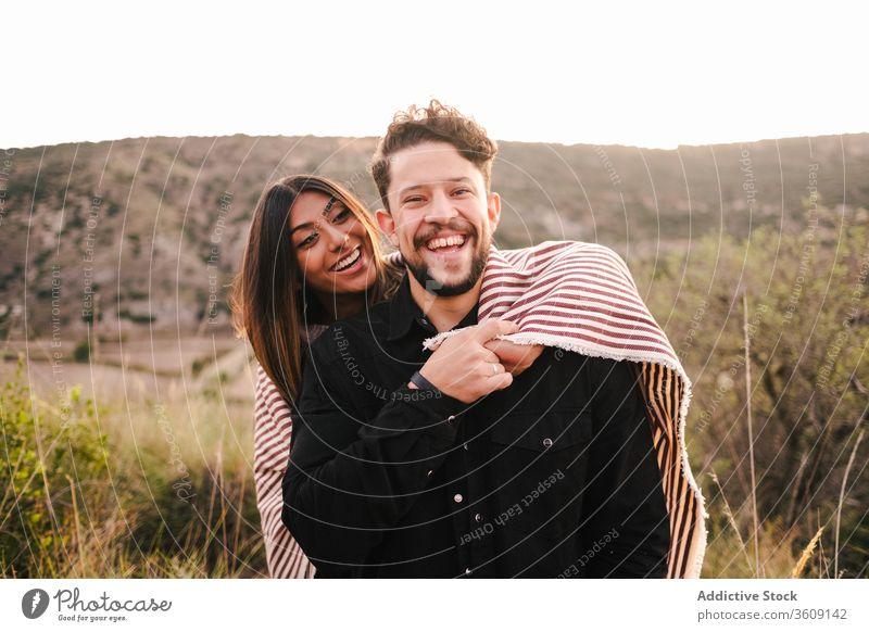 Begeistertes multiethnisches Paar auf dem Hügel Lachen Witz Zusammensein Spaß haben Berge u. Gebirge umarmend heiter Partnerschaft rassenübergreifend vielfältig