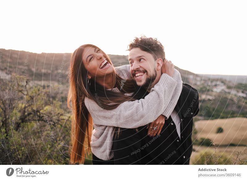 Begeistertes multiethnisches Paar auf dem Hügel Lachen Witz Zusammensein umarmend Spaß haben Berge u. Gebirge Händchenhalten heiter Partnerschaft