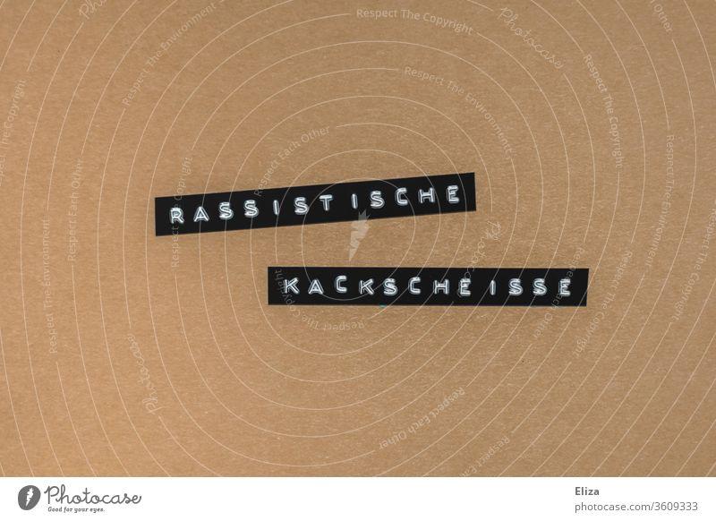 Rassistische Kackscheisse. Text geschrieben auf braunem Hintergrund. Rassismus. Protest. Scheiße Worte gelb Wut Kritik protest black lives matter