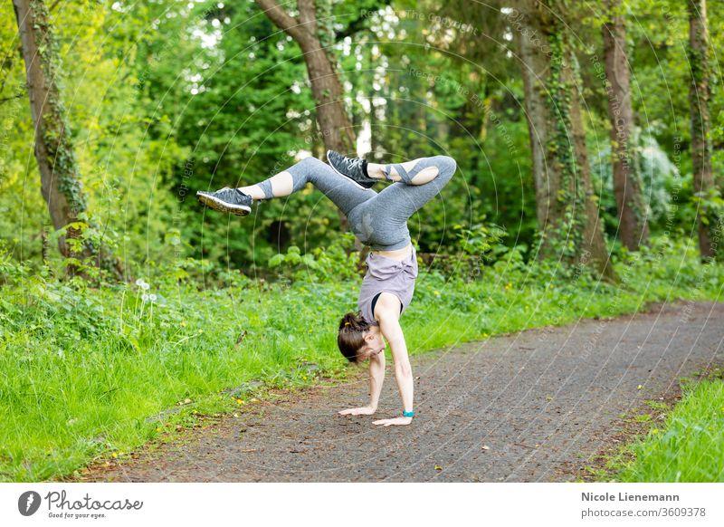Junge Frau macht einen Handstand als Fitnesstraining Training Sport passen im Freien Natur außerhalb aktiv Bewegung rennen Gesundheit Lifestyle Übung Joggen