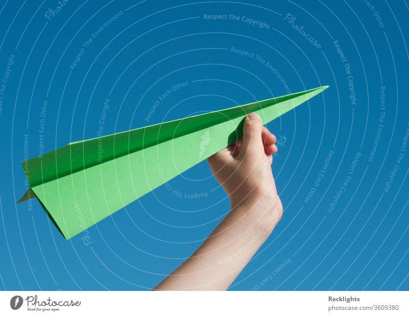 Grünes Reisekonzept mit einem grünen Papierflugzeug gegen blauen Himmel Flugzeug Aspirationen Jungen Kind fliegen Inspiration Freiheit menschlich Hand Ideen