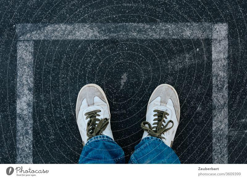 Weiße Sneaker auf Asphalt in rechteckiger Begrenzung aus weißen Linien weiss Rechteck Grenze Stop Halt Anhalten Schnürsenkel Jeans Ausweg Markierung