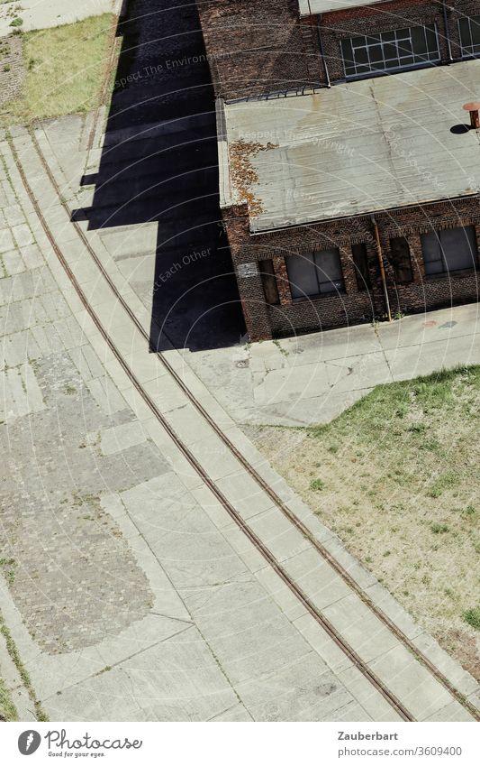 Blick auf die Schienen einer Werksbahn von oben mit alten Fabrikgebäuden Bogen Eisenbahn Gebäude Gleise Industrie historisch Industriedenkmal Industrieanlage