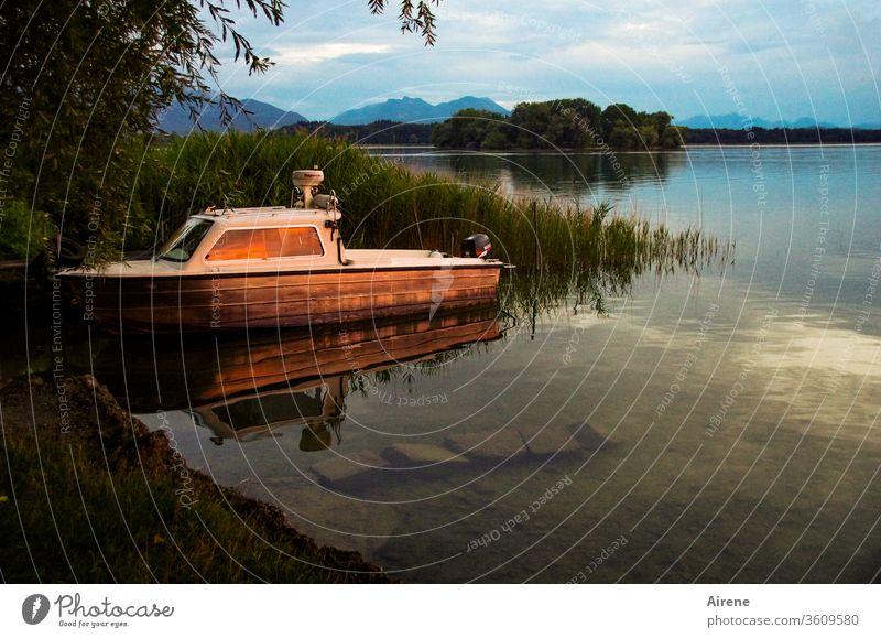Der schnelle Tag ist hin See Seeufer Abend Boot Abendrot Schiff Insel Berge Idylle Stille Sonnenuntergang Sonnenlicht ruhig Ufer Schilf innehalten Trost