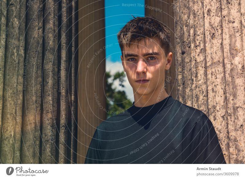 Porträt eines jungen Mannes, der zwischen antiken Säulen steht Teenager männlich im Freien Ständer Architektur schön schwarz blau Junge lässig Kaukasier