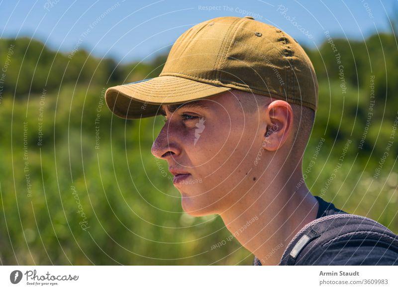 Porträt eines jungen Mannes mit Basecap im Profil zielen Rucksack Baseballmütze Strand schön Junge lässig Kaukasier selbstbewusst Abend Tor grün Reise Lifestyle