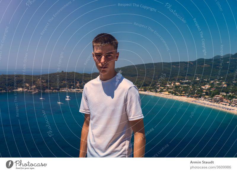 Porträt eines selbstbewussten jungen Mannes mit dem Strand der Stadt Parga im Hintergrund schön blau Junge lässig Kaukasier wolkenlos Reise Lifestyle Blick