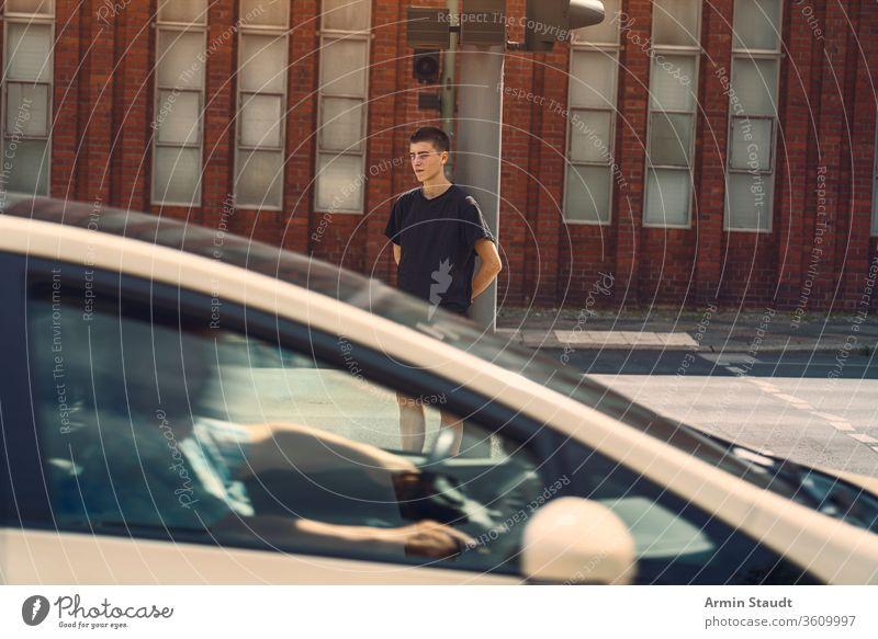 Porträt eines einsamen jungen Mannes, bei dem ein Auto durch das Bild fährt Jugendlicher schön Junge Gebäude PKW lässig Kaukasier selbstbewusst Kultur Laufwerk