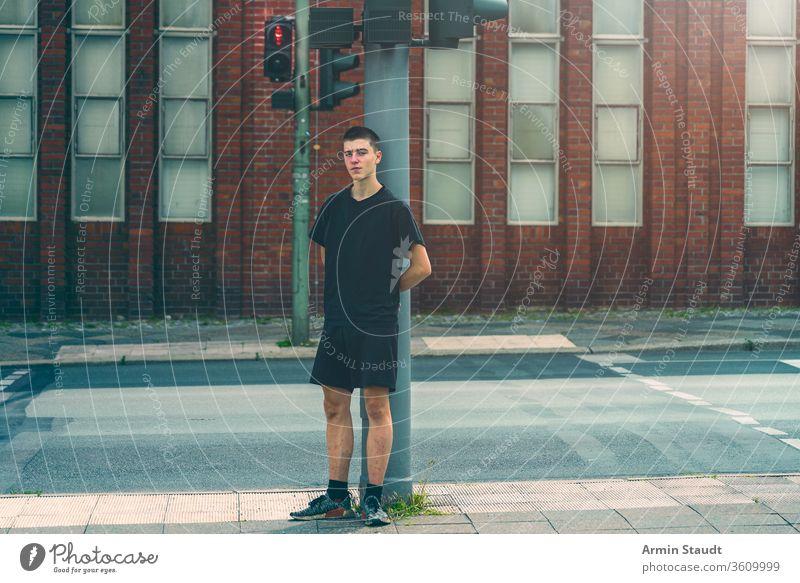 Porträt eines einsamen jungen Mannes, der an einer roten Ampel steht Straße Jugendlicher schön Junge Gebäude lässig Kaukasier selbstbewusst Kultur Zukunft