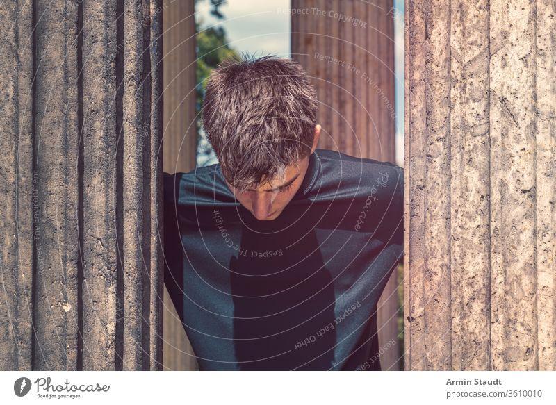 Porträt eines jungen Mannes, der zwischen antiken Säulen steht und nach unten schaut Teenager Lifestyle Reise Ständer Architektur im Freien schön schwarz blau