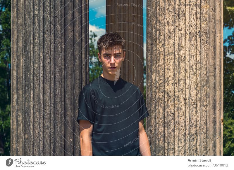 Porträt eines jungen Mannes, der zwischen antiken Säulen steht Architektur schön schwarz blau Junge lässig Kaukasier Kleidung Konzentration selbstbewusst Reise
