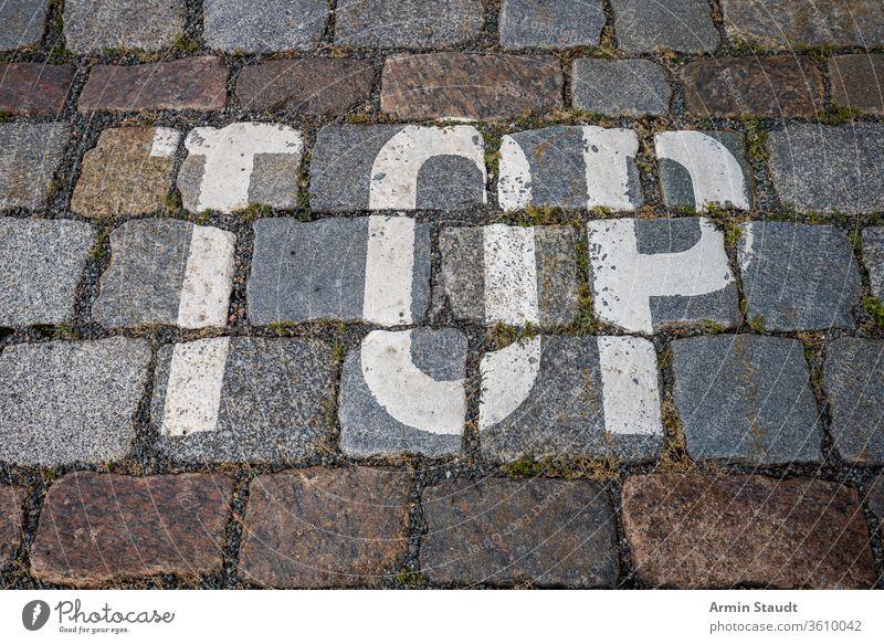 das Wort oben mit weißer Farbe auf Kopfsteinpflaster für Hintergründe abstrakt Alphabet Hintergrund Großstadt Nahaufnahme Design Stock Grunge Andeutung Briefe