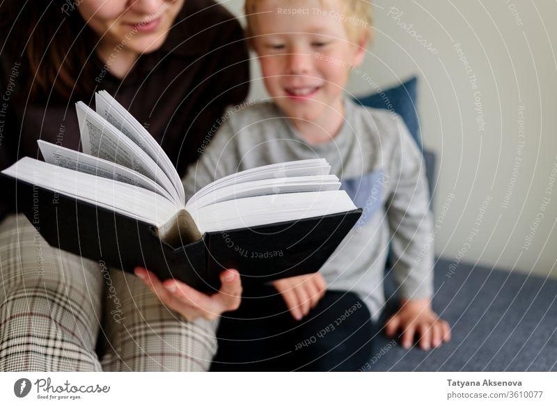 Mutter und Kind lesen Buch und lächeln Familie heimwärts Zusammensein Glück Kindheit Menschen Eltern Frau Kaukasier Bildung Fröhlichkeit im Innenbereich Mama