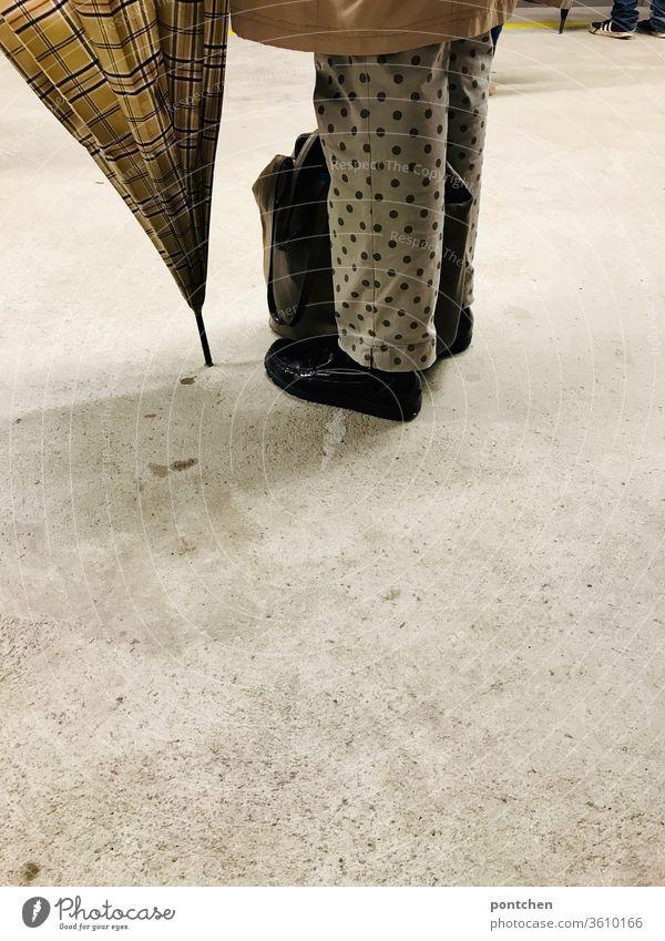 Mustermix- Punkte und Karos. Unterkörper einer älteren Frau mit Regenschirm. Mode, Stil. regenschirm hose gepunktet kariert bingham muster unterkörper beine