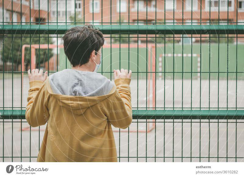 Rückansicht eines traurigen Kindes, das auf den Fussballplatz schaut Coronavirus Virus Seuche covid-19 Fußball Tor Ball Spielplatz Spielzeit Pandemie Quarantäne