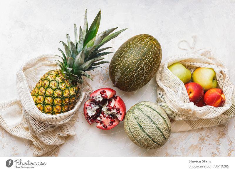 Frische Früchte der Saison (Ananas, grüne Äpfel, Granatapfel, Pfirsiche und Melone) in umweltfreundlichen und wiederverwendbaren Einkaufsnetztaschen. Gesunde vegane Ernährung. Null Abfall