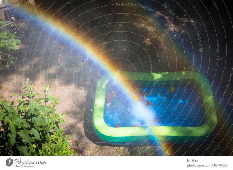 Planschbecken in einem Garten mit Regenbogen und Wassertropfen. Vogelperspektive Spielzeug Kindheit abkühlung regenbogenfarben warme jahreszeit Busch Baum gelb