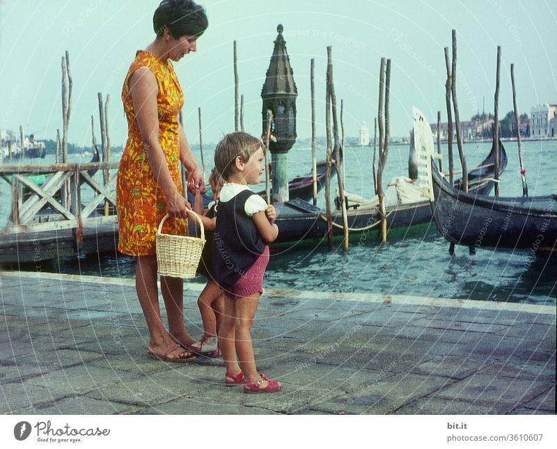 alt l Hübsche, junge, modische Mutter mit zwei Töchtern im Sommerurlaub, stehen im Hafen von Venedig. Mutter mit Kindern beobachtet neugierig Schiffe und Boote im Meer. Familienausflug in Italien in den 60er Jahren. Nostalgisches, altes 60er Familienphoto