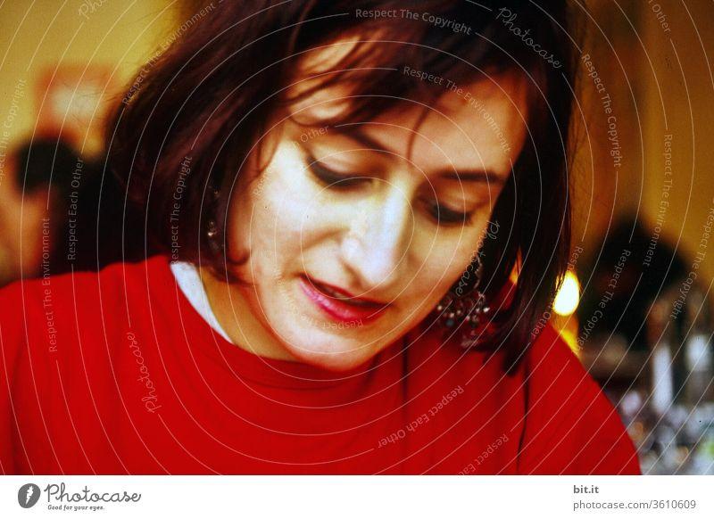 Junge Frau mit Blick nach unten sitzt drinnen an einem Tisch und schreibt. Frau mit rotem Pullover, schwarzen langen Haaren schaut nach unten, zuhause in der Wohnung. Erwachsene Frau zeichnet, lächelnd und konzentriert, bei warmen, gemütlichen Licht..