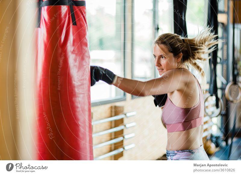 Junge sportliche Frau beim Boxen in der Turnhalle {Lebensstil Sport zäh Stanzen aktiv Konkurrenz blond Motivation Trainerin Gesundheit Handschuhe Ausdauer
