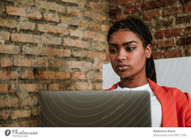 Moderne schwarze Frau mit Computer im Sessel Business Laptop online elegant Loft Design Fokus Innenbereich freiberuflich modern Gerät Apparatur Internet