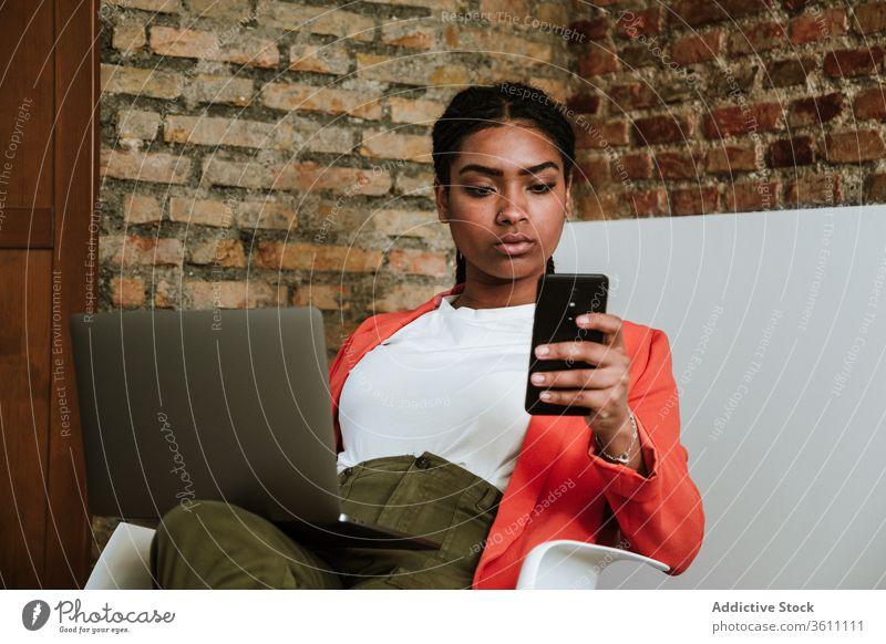 Moderne schwarze Frau mit Gadgets im Sessel Business Laptop heiter Smartphone online elegant Computer Loft Design Innenbereich freiberuflich modern Glück Gerät