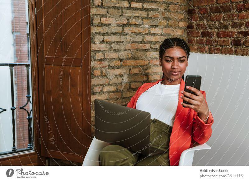 Lächelnde moderne schwarze Frau mit Gadgets im Sessel Business Laptop heiter Smartphone online elegant Computer Loft Design Innenbereich freiberuflich Glück