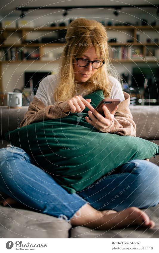 Nutzpflanzenfrau surft zu Hause auf einem Smartphone Browsen Frau heimwärts Surfen Funktelefon Wochenende unterhalten benutzend Touchscreen gemütlich Gerät