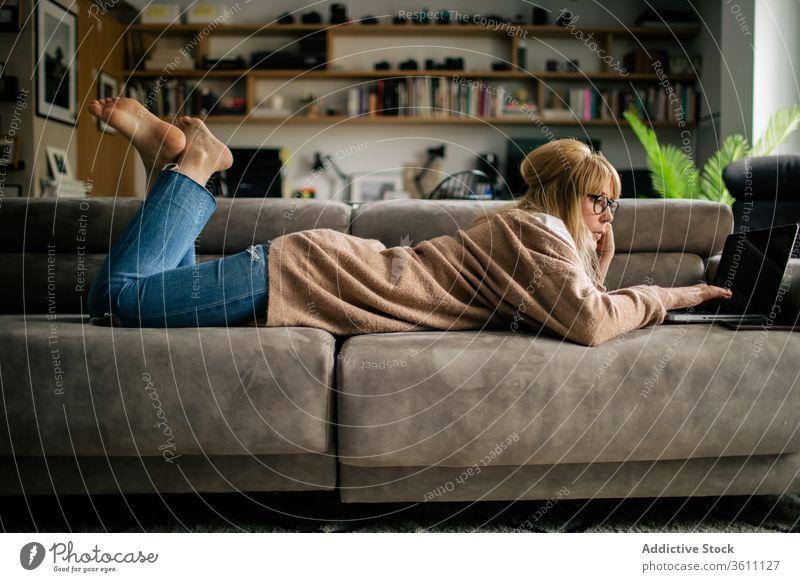 Nachdenkliche Frau arbeitet zu Hause am Laptop Browsen freiberuflich Projekt benutzend Telearbeit Lügen Sofa Arbeit abgelegen ernst Brille Apparatur Internet
