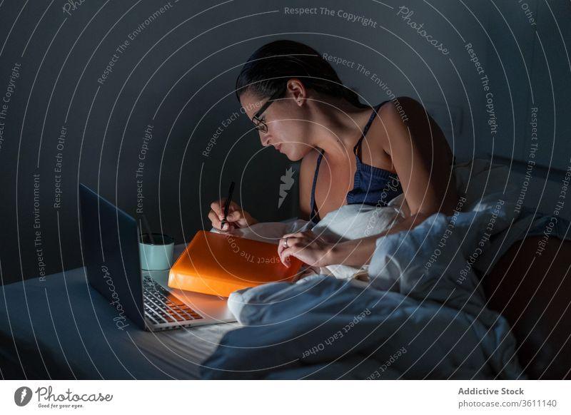 Vielbeschäftigte Freiberuflerin, die im Bett arbeitet Geschäftsfrau freiberuflich Frau Arbeit Nacht abgelegen Laptop Browsen benutzend Unternehmer liegend