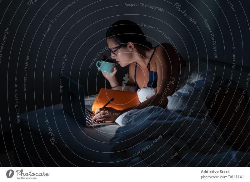 Vielbeschäftigte Freiberuflerin, die im Bett arbeitet Geschäftsfrau freiberuflich Frau Arbeit Nacht abgelegen Laptop Browsen trinken benutzend Kaffee