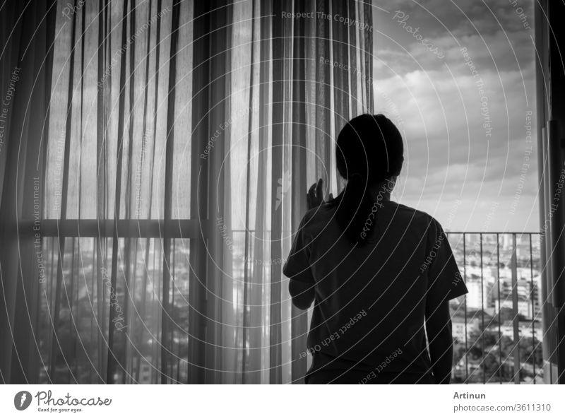 Traurige erwachsene asiatische Frau, die aus dem Fenster schaut und nachdenkt. Gestresste und depressive junge Frau. Verzweifelte Frauen mit langen Haaren und T-Shirts, die am Fenster des Hauses oder Krankenhauses stehen. Einsam und ängstlich.